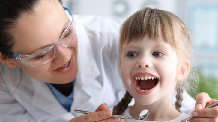 Kieferorthopäden schaut in den Mund eines kleinen Mädchens